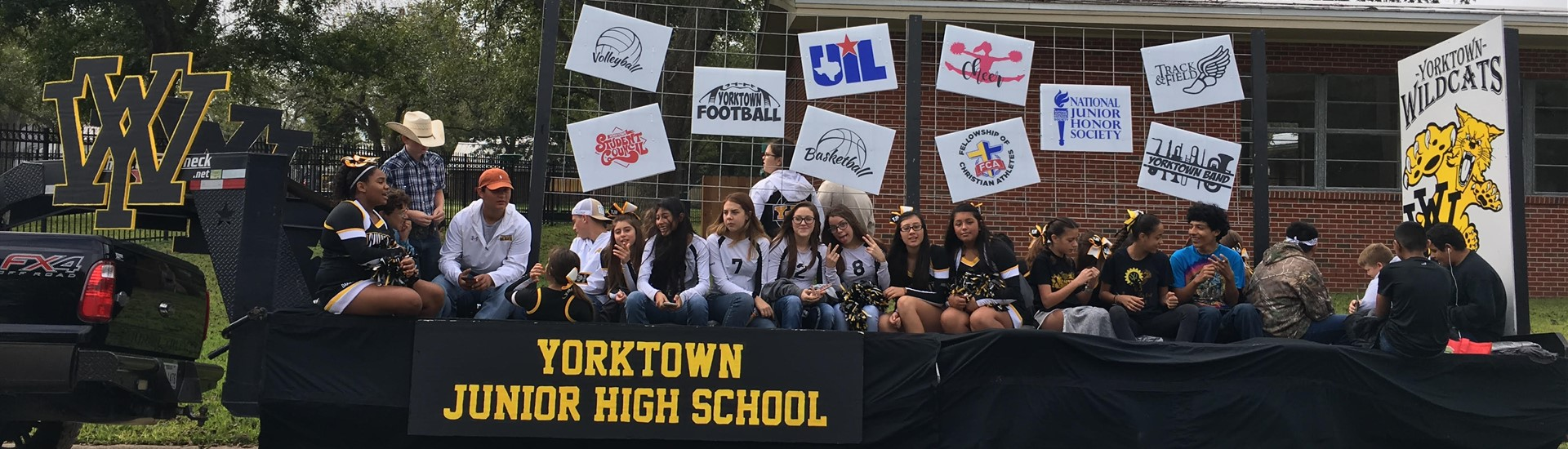Junior High students on the 2018 Western Days parade float, displaying signs for various extracurricular activities and organizations.